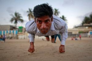 Ram Pratap Verma, a 32-year-old aspiring Bollywood film actor, practices gymnastics on a beach in Mumbai